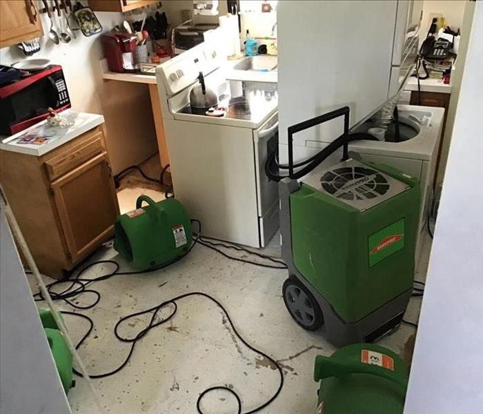 Kitchen with removed floors, detached appliances, and SERVPRO branded large capacity dehumidifier/ air movers neatly arranged